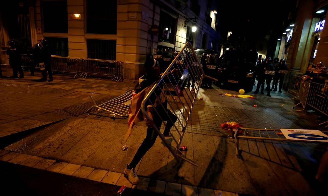 Um manifestante joga uma cerca nos confrontos com a polícia Foto: RAFAEL MARCHANTE / REUTERS