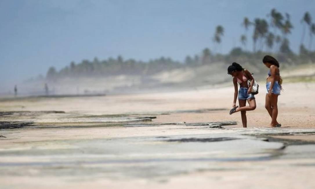 Banhistas em Conde, na Bahia; no Estado, órgão emitiu um alerta para que praias contaminadas com óleo sejam evitadas Foto: REUTERS/ADRIANO MACHADO