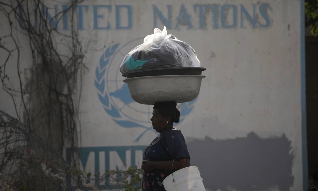 Mulher passa por um sinal da Nações Unidas na capital do Haiti, Port-au-Prince: todos os indicadores econômicos e sociais do país, o mais pobre das Américas, estão no vermelho Foto: ANDRES MARTINEZ CASARES/REUTERS
