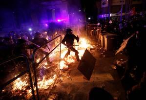 Polícia avança contra barricada montada por manifestantes em uma rua de Barcelona. Protestos bloquearam estradas e o principal aeroporto da região Foto: ALBERT GEA / REUTERS