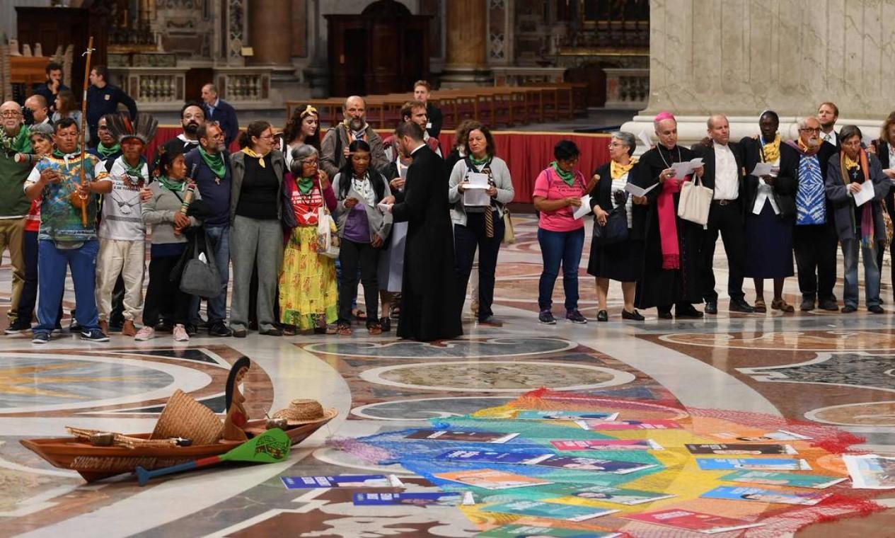 Participantes do sínodo da Amazônia e representantes dos povos indigenas na Basílica de São Pedro, Vaticano, reunidos em torno de uma barca de madeira que representa a Amazônia Foto: ANDREAS SOLARO / AFP