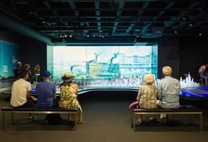 Visitantes no Chicago Architecture Center assistem a uma apresentação multimídia sobre o desenvolvimento da cidade Foto: Michelle Litvin / The New York Times