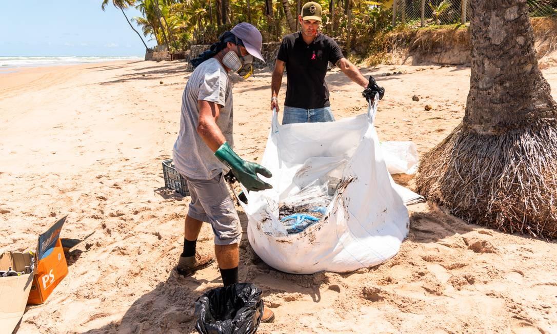 O óleo sendo embalado para descarte pelos voluntários na praia de Jauá, Camaçari Foto: Mateus Morbeck / Mateus Morbeck