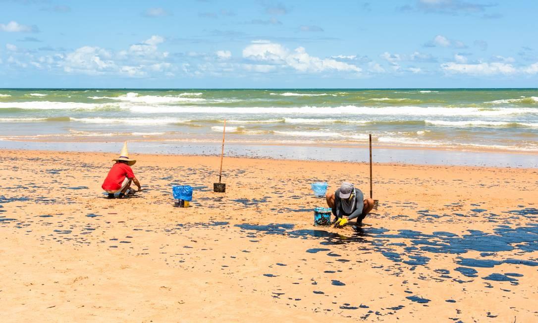 Integrantes do Guardiões do Litoral trabalham na retirada do óleo da praia de Camaçari Foto: Mateus Morbeck / Mateus Morbeck