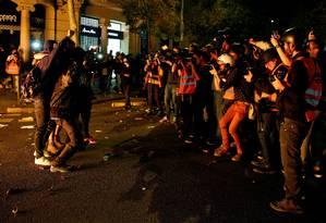 Alheios ao caos nas ruas, grupo de manifestantes posa para um grupo de jornalistas em Barcelona. Protestos chegaram à quarta noite consecutiva e prefeitura da cidade contabiliza os prejuízos Foto: RAFAEL MARCHANTE / REUTERS