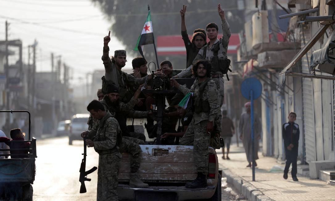 Rebeldes sírios apoiados pela Turquia acenam na traseira de uma caminhonete na cidade fronteiriça de Tal Abyad, na Síria. Uma semana após iniciar uma operação militar no Nordeste do país, a Turquia aceitou um cessar-fogo, mediado pelos EUA, em meio a combates com forças curdas e do Exército sírio Foto: KHALIL ASHAWI / REUTERS
