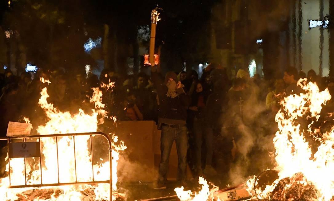 Manifestantes gesticulam atrás de barricadas em chamas em Barcelona. O governo da Catalunha voltou a defender independência em nova noite de protestos Foto: LLUIS GENE / AFP