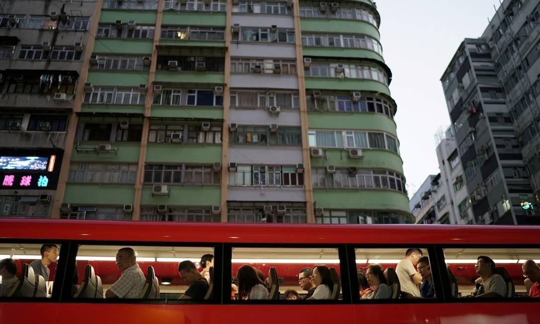 Passageiros vistos pelas janelas de um ônibus de dois andares enquanto atravessa uma rua principal de Argyle, em Hong Kong, na China Foto: Umit Bektas / REUTERS