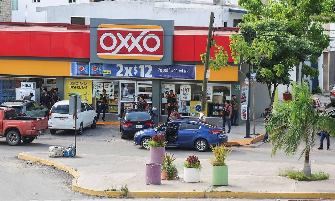 """Homens do Cartel de Sinaloa diante de uma loja durante o confronto com forças federais após a detenção de Ovidio Guzmán, filho do chefão das drogas Joaquin """"El Chapo"""" Guzmán, em Culiacán, estado de Sinaloa, México Foto: JESUS BUSTAMANTE / REUTERS"""