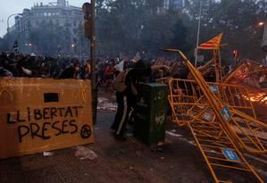 Manifestantes montam barricadas nas ruas de Barcelona em meio a novos confrontos com a polícia. Em uma das barreiras o pedido para que os 9 ativistas condenados a até 13 anos de prisão sejam libertados Foto: PAU BARRENA / AFP