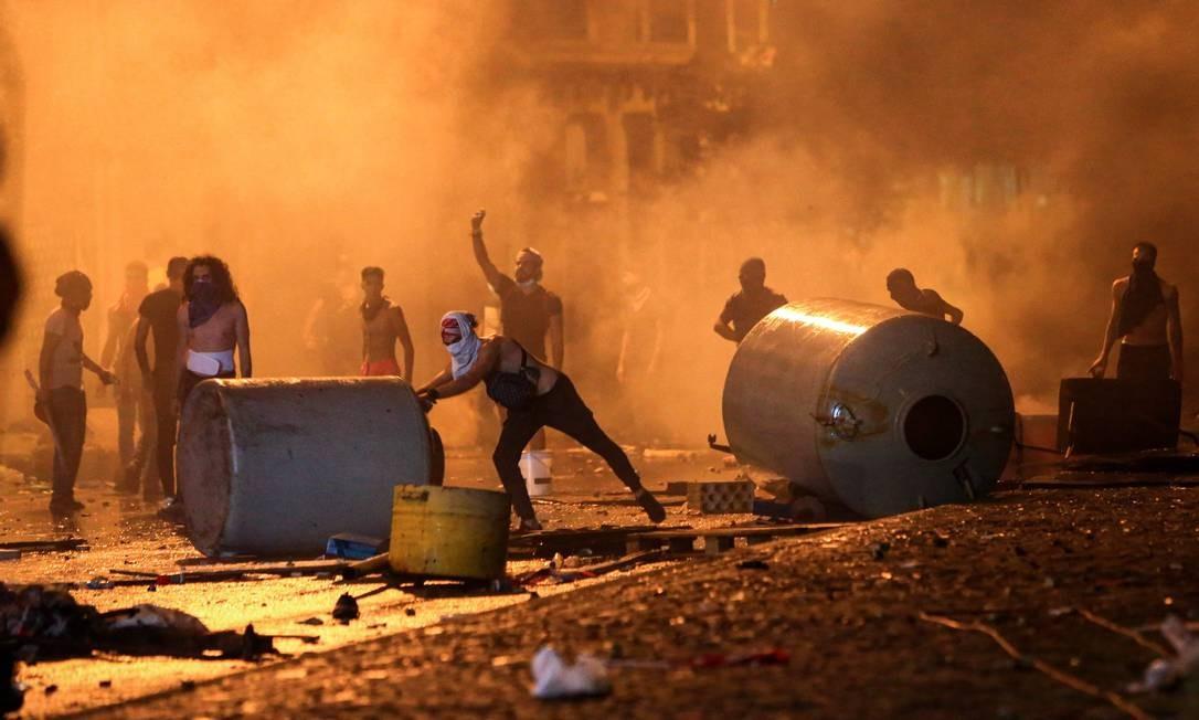 Manifestantes libaneses criam uma barricada em meio a confrontos com forças de segurança na Praça Riad al-Solh, em Beirute Foto: - / AFP