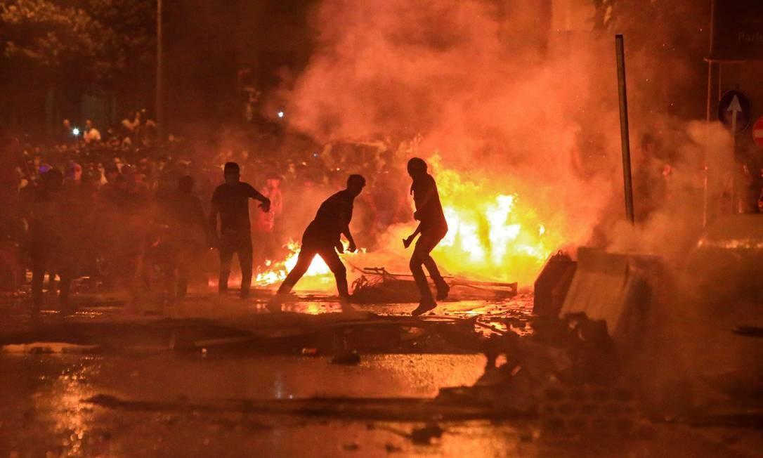Manifestantes libaneses montam barricada de fogo em meio a confrontos com forças de segurança. Milhares de libaneses bloquearam as principais rodovias com pneus queimados pelo segundo dia para protestar contra a corrupção Foto: STR / AFP