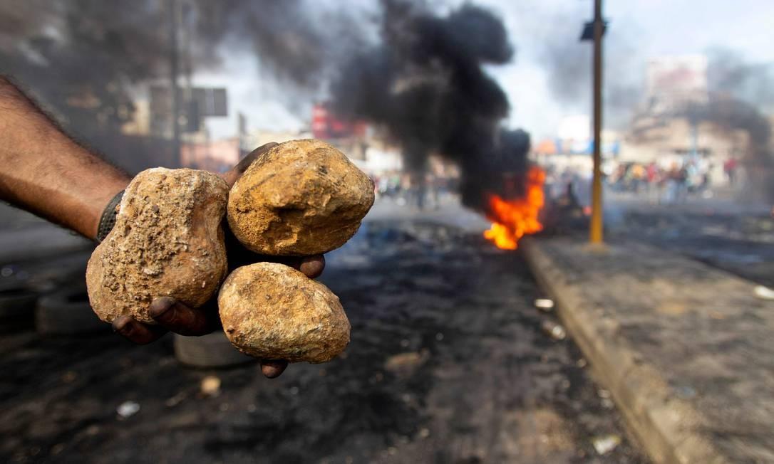 Um manifestante libanês carrega pedras durante um protesto Foto: IBRAHIM AMRO / AFP