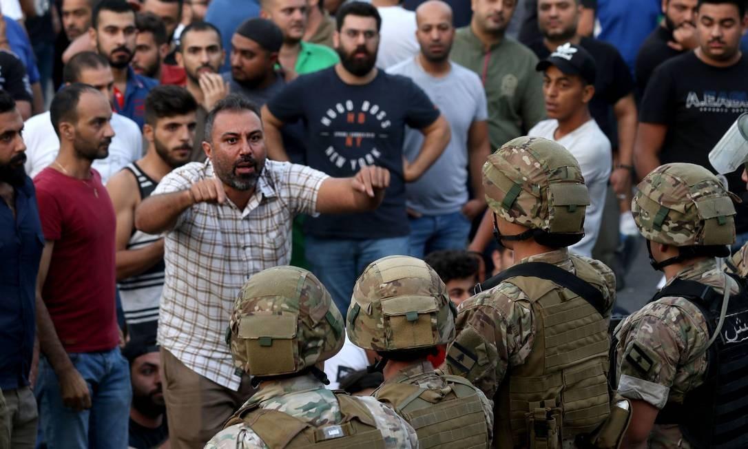 Forças de segurança libanesas montam guarda para conter manifestantes na cidade portuária libanesa de Sidon Foto: AFP