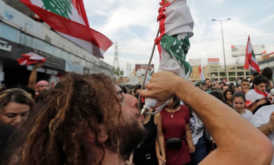 Manifestante libanês toca um berrante adornado com a bandeira nacional durante protesto em Zouk Mikael Foto: JOSEPH EID / AFP