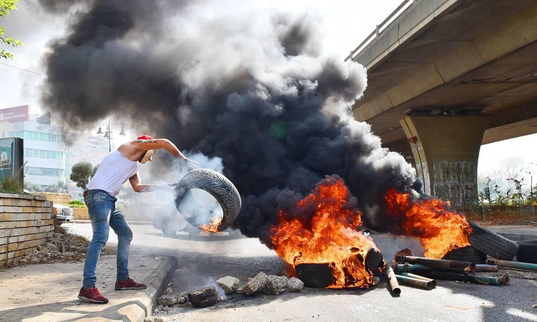 Manifestante libanês atira um pneu em um incêndio que bloqueia uma estrada perto do Aeroporto Internacional Beirute-Rafic Hariri, em meio a protestos em andamento contra condições econômicas difíceis do país Foto: - / AFP