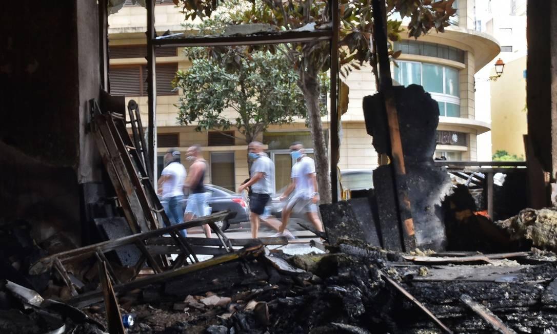 Homens mascarados passam por uma loja incendiada ao longo de uma estrada no centro da capital libanesa Foto: - / AFP