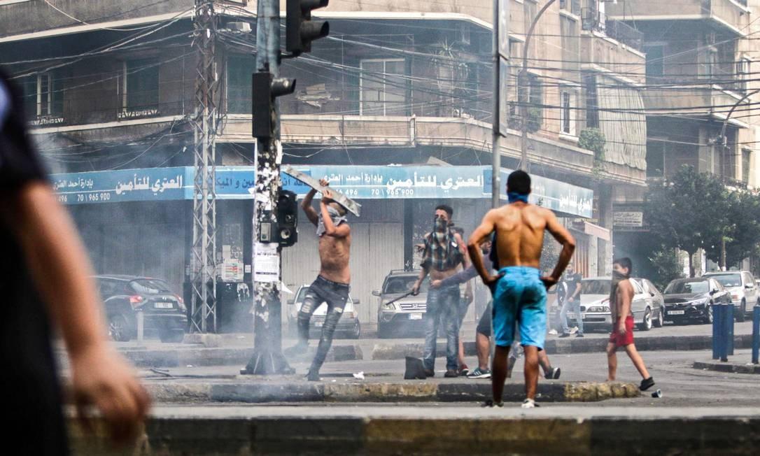 Manifestantes libaneses quebram semáforos em meio a protestos na cidade costeira de Trípoli Foto: IBRAHIM CHALHOUB / AFP