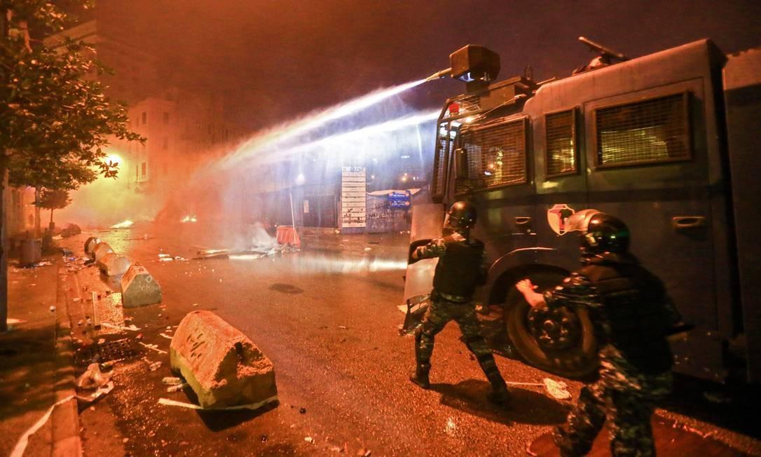 Forças de segurança libanesas disparam jato d'água contra manifestantes na Praça Riad al-Solh, no centro de Beirute Foto: STR / AFP