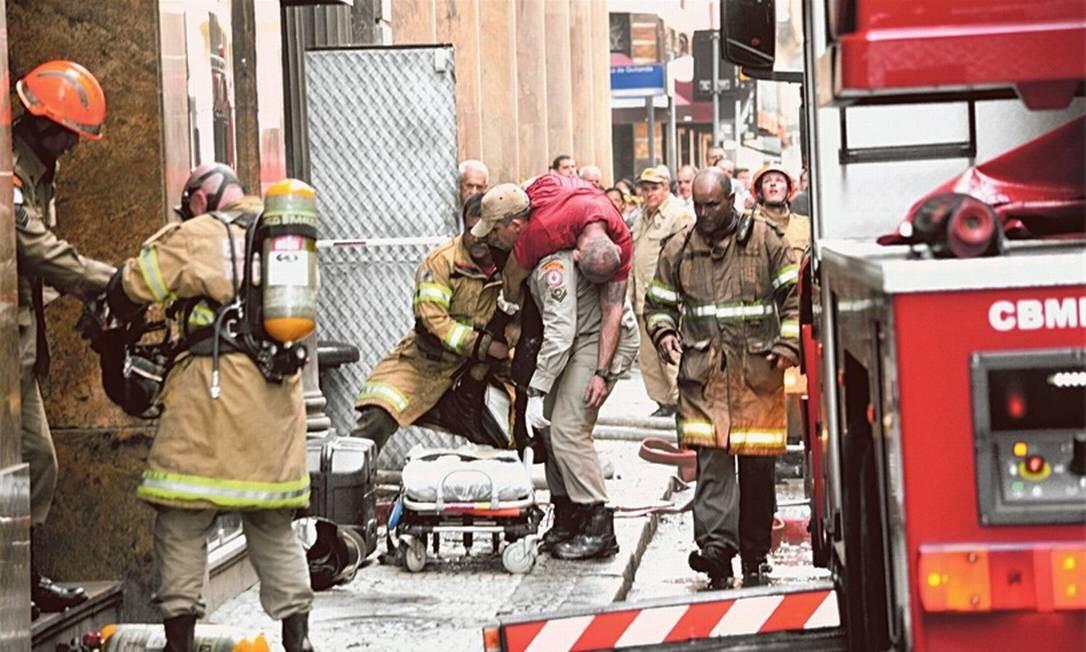 Tragédia: bombeiro carrega colega em incêndio ocorrido no Centro do Rio Foto: Jorge Hely / Framephoto