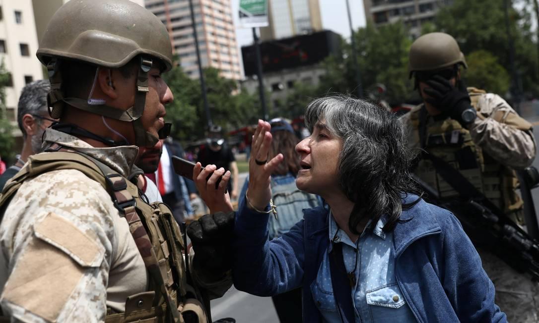 Manifestante discute com militar nas ruas de Santiago, horas depois do decreto de estado de emergência na capital, uma medida que, na democracia, só foi usada em situações de desatre natural Foto: EDGARD GARRIDO / REUTERS