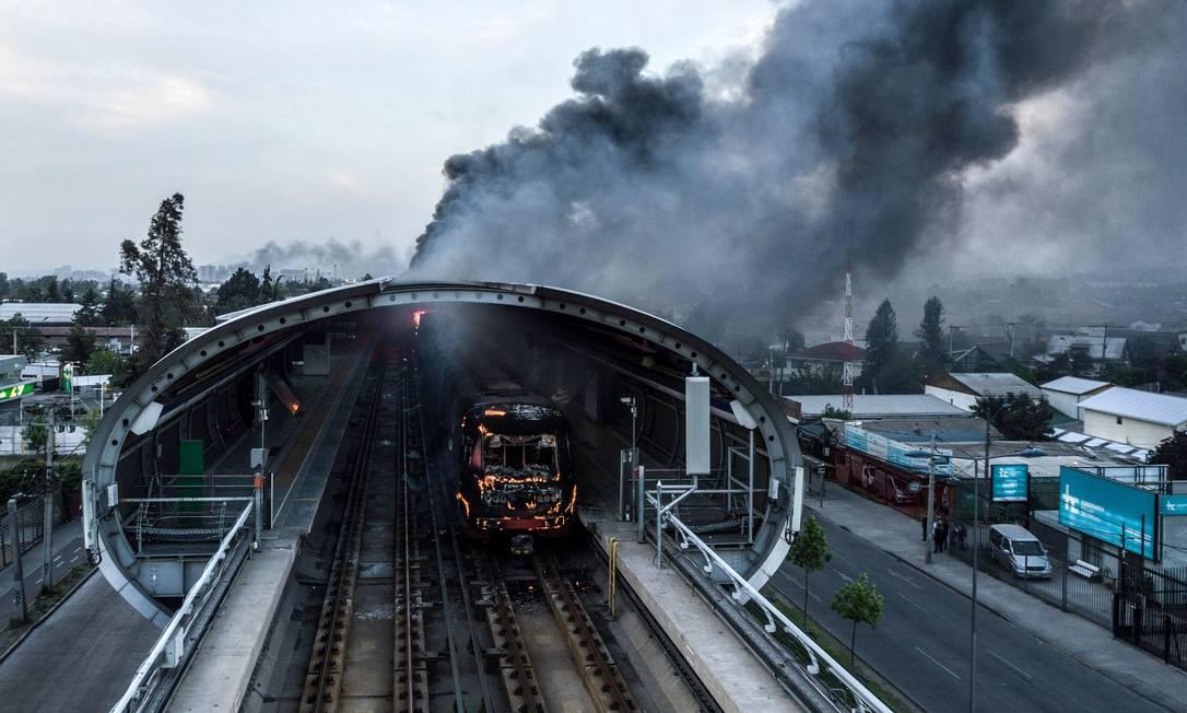 Estação de metro atacada durante os protestos deste sábado em Santiago. Governo decretou toque de recolher na cidade até a manhã de domingo Foto: JAVIER TORRES / AFP