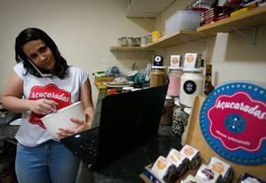 Karen Luz se divide entre o computador e os doces Foto: Pablo Jacob / Agência O Globo