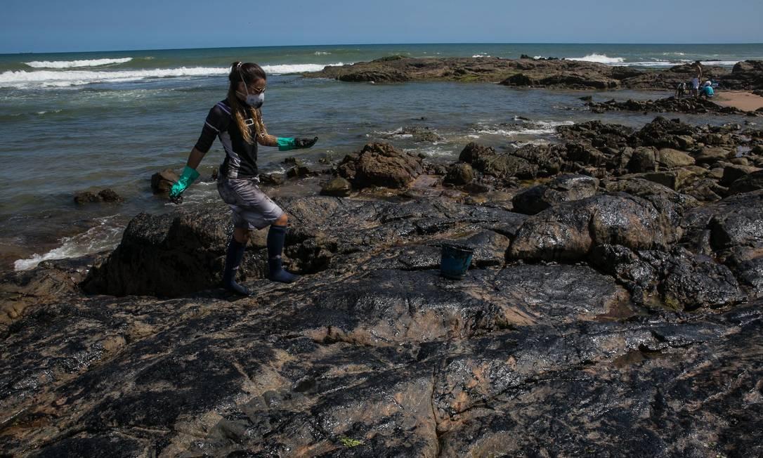 Voluntária recolhe o óleo na praia de Pedra do Sal, Bahia, que cobriu as pedras Foto: ANTONELLO VENERI / AFP