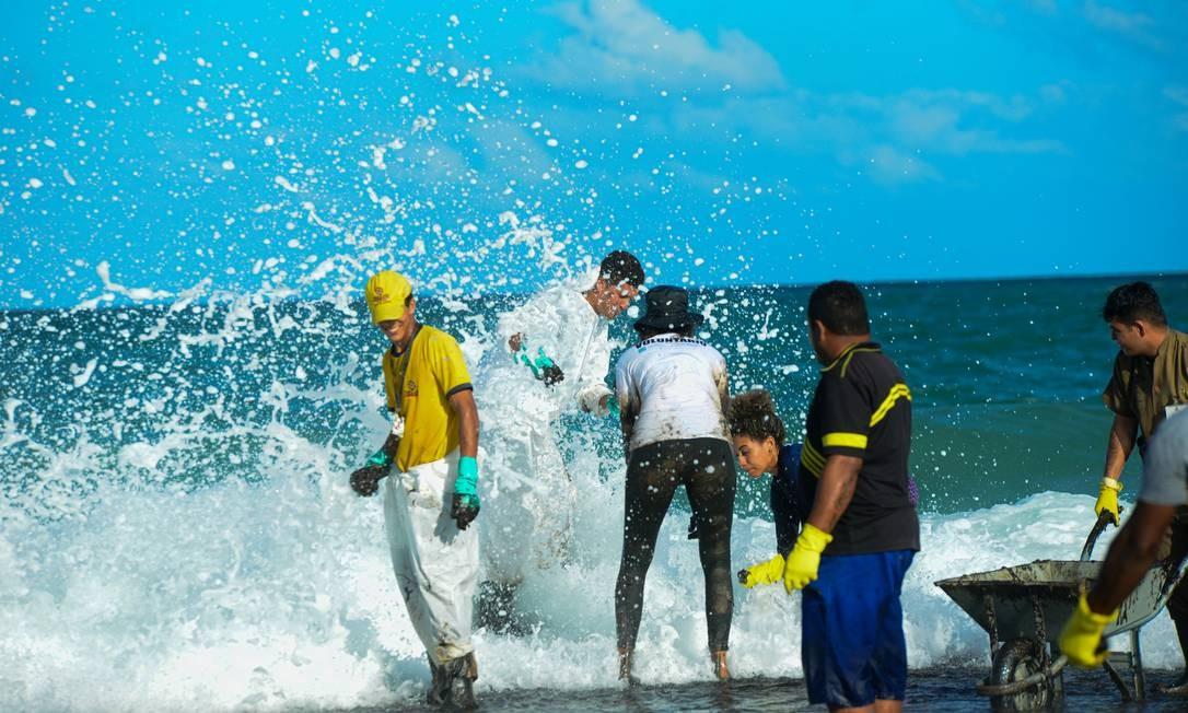 O trabalho de recolhimento do óleo em Muro Alto, Tamandaré, Pernambuco Foto: STRINGER / REUTERS