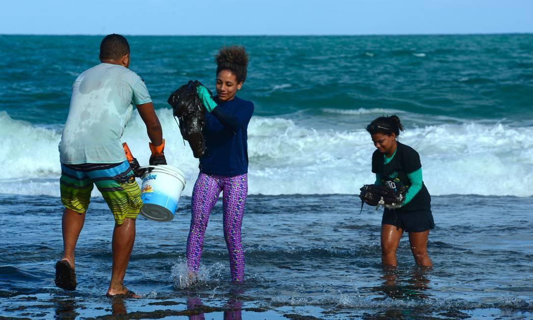 Os voluntários também retiram o óleo que está na beira d'água em Muro Alto, Tamandaré, Pernambuco Foto: STRINGER / REUTERS