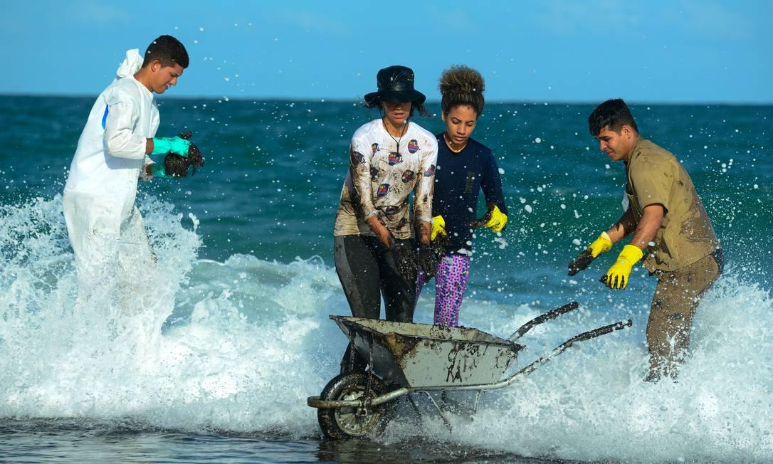 Voluntários trabalham na remoção do óleo na praia de Muro Alto, no município de Tamandaré, Pernambuco, um carrinho de mão é usado para reitrar o óelo do mar Foto: STRINGER / REUTERS