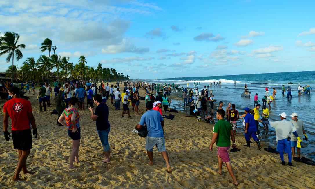 Dezenas de pessoas ajudam a recolher o óleo na praia de Muro Alto, em Tamandaré, Pernambuco Foto: STRINGER / REUTERS