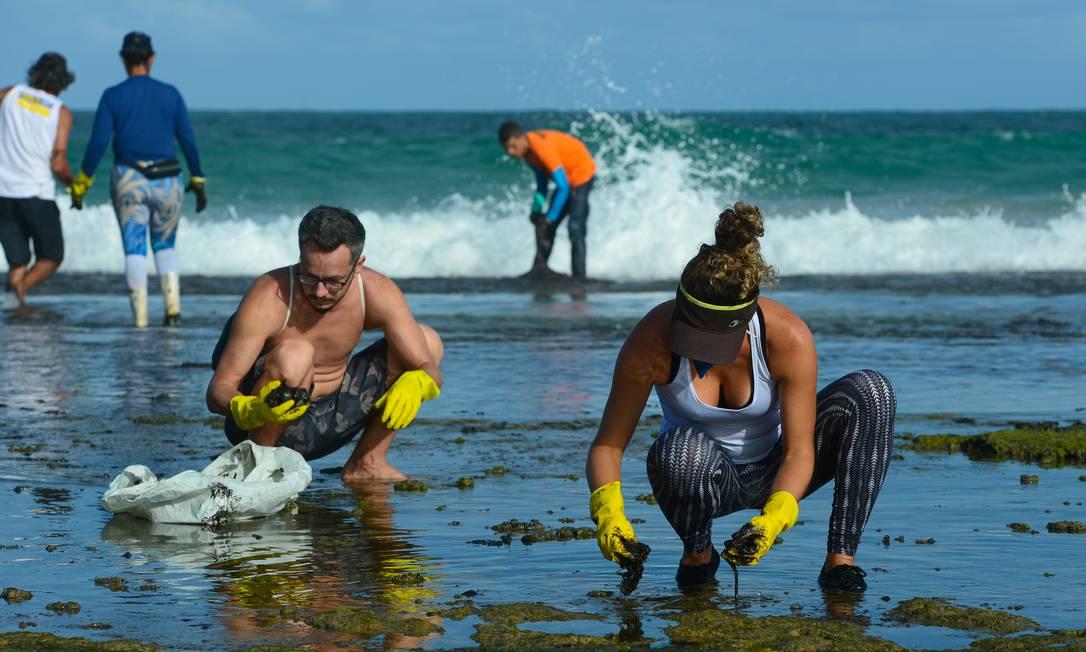 O óleo que chega na praia sendo retirado por voluntários em Muro Alto, em Tamandaré, Pernambuco Foto: STRINGER / REUTERS