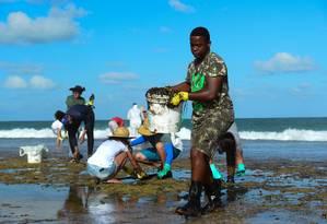 Pessoas trabalham para remover óleo da praia de Muro Alto, em Tamandaré, Pernambuco Foto: STRINGER / REUTERS