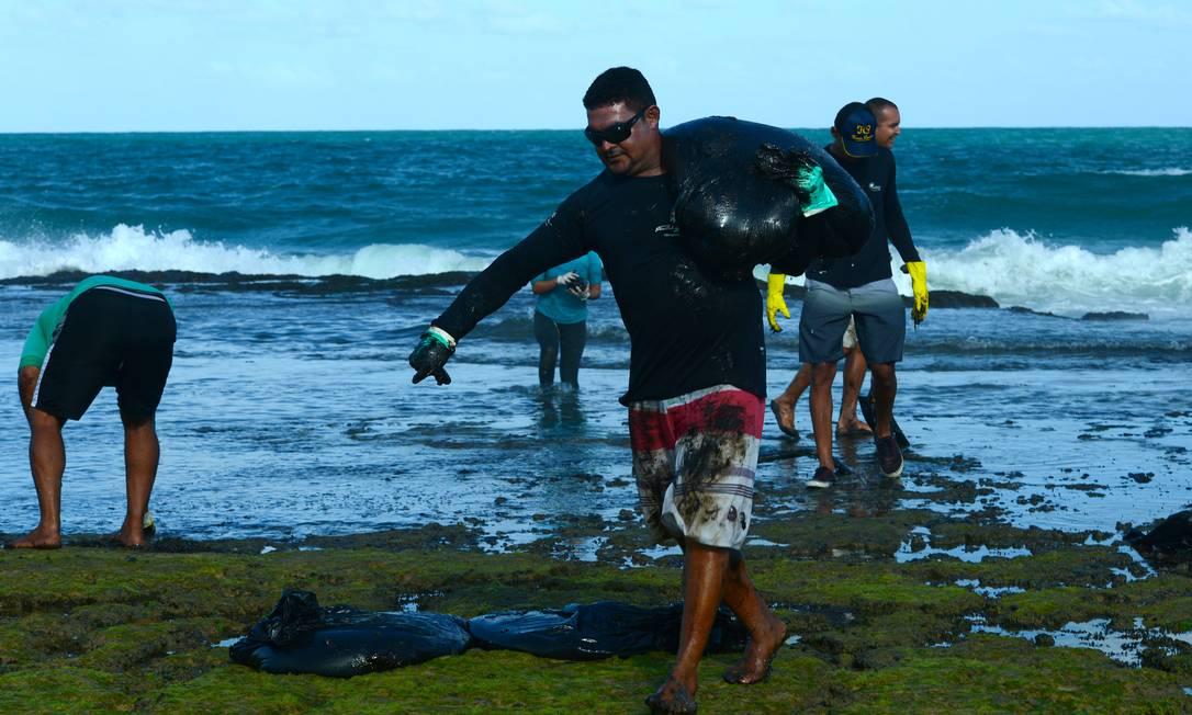 Voluntário carrega uma bola de óleo retirada do mar da praia de Muro Alto, Tamandaré, Pernambuco Foto: STRINGER / REUTERS