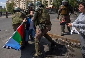 Policiais prendem manifestante durante protestos em Santiago: governo estendeu toque de recolher Foto: CLAUDIO REYES / AFP