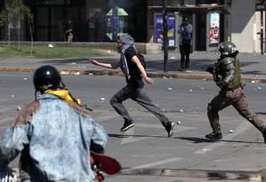 Policial persegue manifestante durante um protesto em Santiago Foto: IVAN ALVARADO / REUTERS