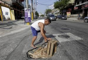 Buraco no asfalto na Avenida Manuel Nogueira de Sá, em Sulacap. Queda nos investimentos prejudica manutenção Foto: Marcos Ramos / Agência O Globo