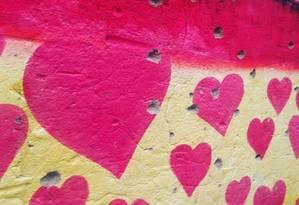 As marcas de tiros no muro onde foram pintados corações Foto: Favela Art / Divulgação