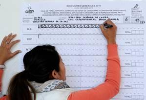 Mulher participa da contagem de votos nas eleições presidenciais da Bolívia em uma seção eleitoral em La Paz: até a manhã desta segunda o TSE boliviano não havia atualizado apuração, que permanece em cerca de 84% das urnas Foto: JORGE BERNAL/AFP