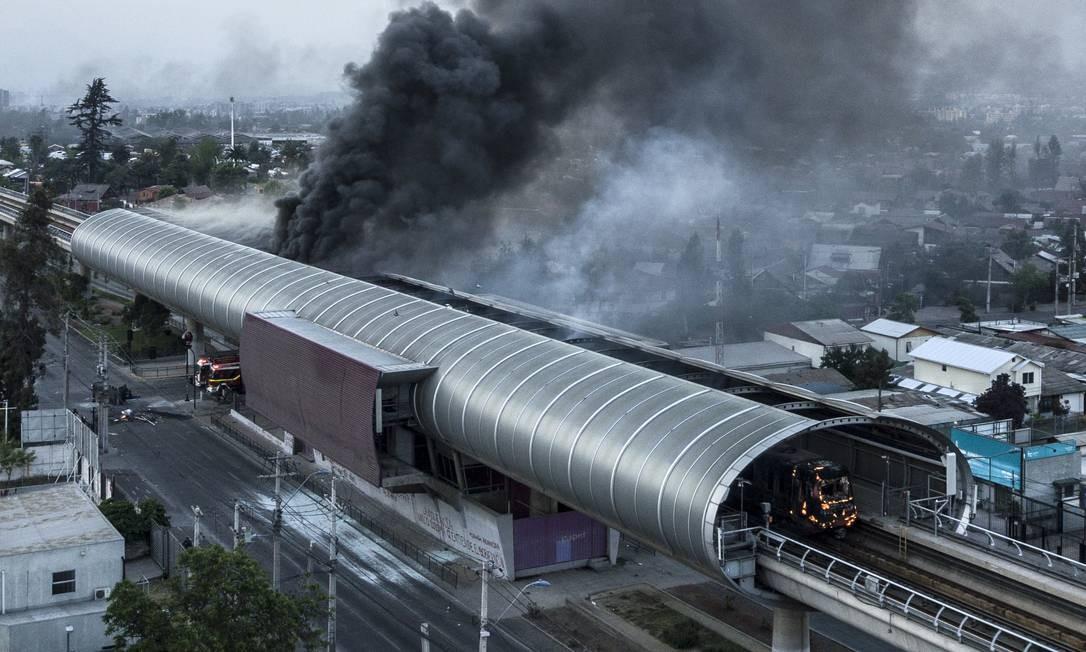 Vista aérea de estação do metrô de Santiago em chamas: aumento das passagens foi estopim do protestos que agitaram o Chile no fim de semana Foto: JAVIER TORRES/AFP/19-10-2019