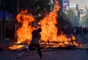 Manifestantes queimam entulho em rua de Santiago durante mais um dia de protestos na cidade Foto: MARTIN BERNETTI / AFP