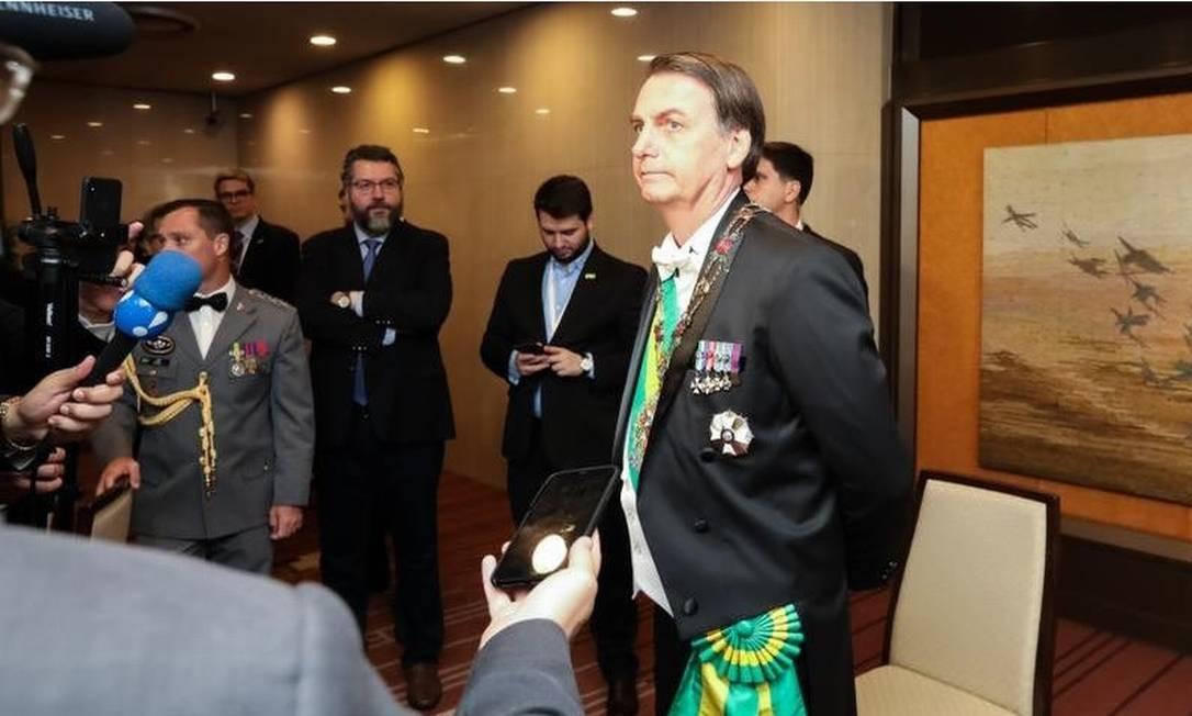 O presidente Jair Bolsonaro fala à imprensa antes de se dirigir à cerimônia de entronização do imperador japonês. Ao fundo, de braços cruzados, o ministro de Relações Exteriores, Ernesto Araújo Foto: Divulgação- Presidência da República