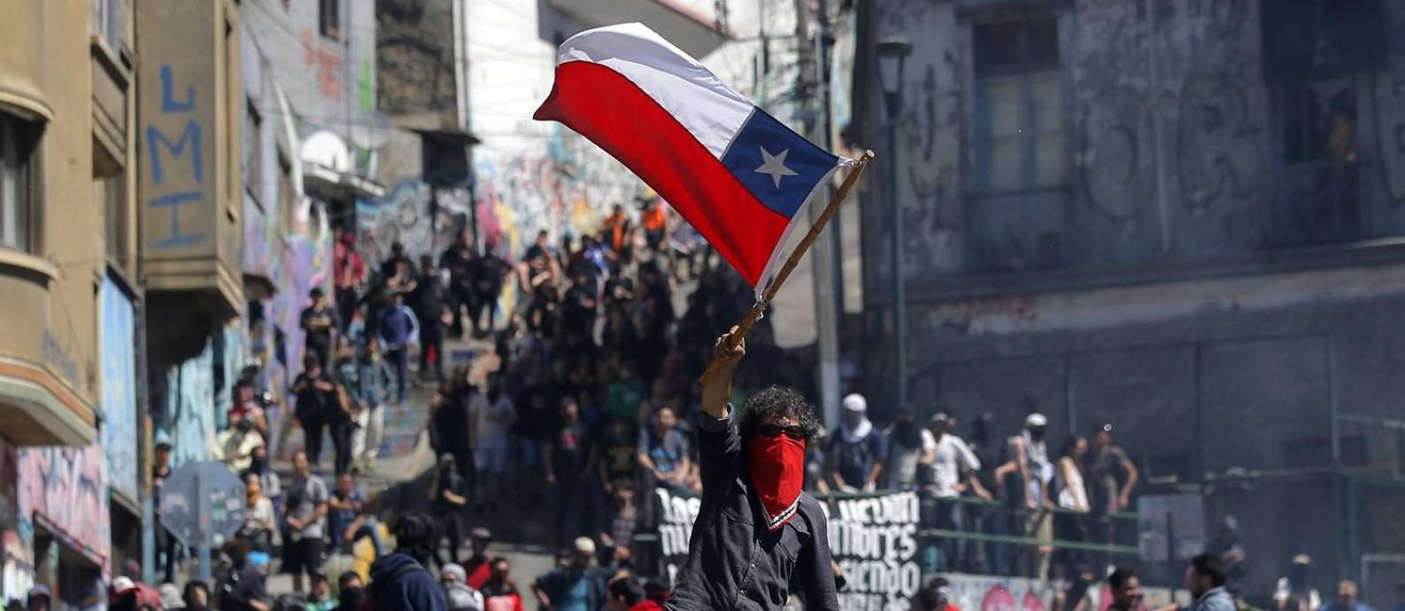 Manifestante ergue a bandeira do Chile em protesto na cidade litorânea de Valparaíso: número de mortos em incidentes relacionados às manifestações chegam a 15, enquanro mais de 1,4 mil pessoas já foram detidas Foto: JAVIER TORRES/AFP/21-10-2019