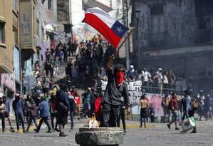 Manifestante ergue a bandeira do Chile em protesto na cidade litorânea de Valparaíso Foto: JAVIER TORRES/AFP/21-10-2019