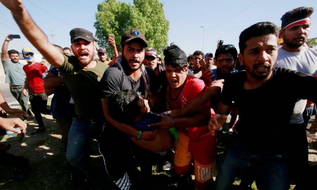 Homens carregam manifestante ferido durante protestos no início de outubro Foto: Alaa Al-Marjani / REUTERS