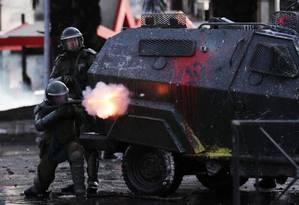 Policial dispara bomba de gás lacrimogêneo durante protestos em Santiago, Chile Foto: IVAN ALVARADO / REUTERS