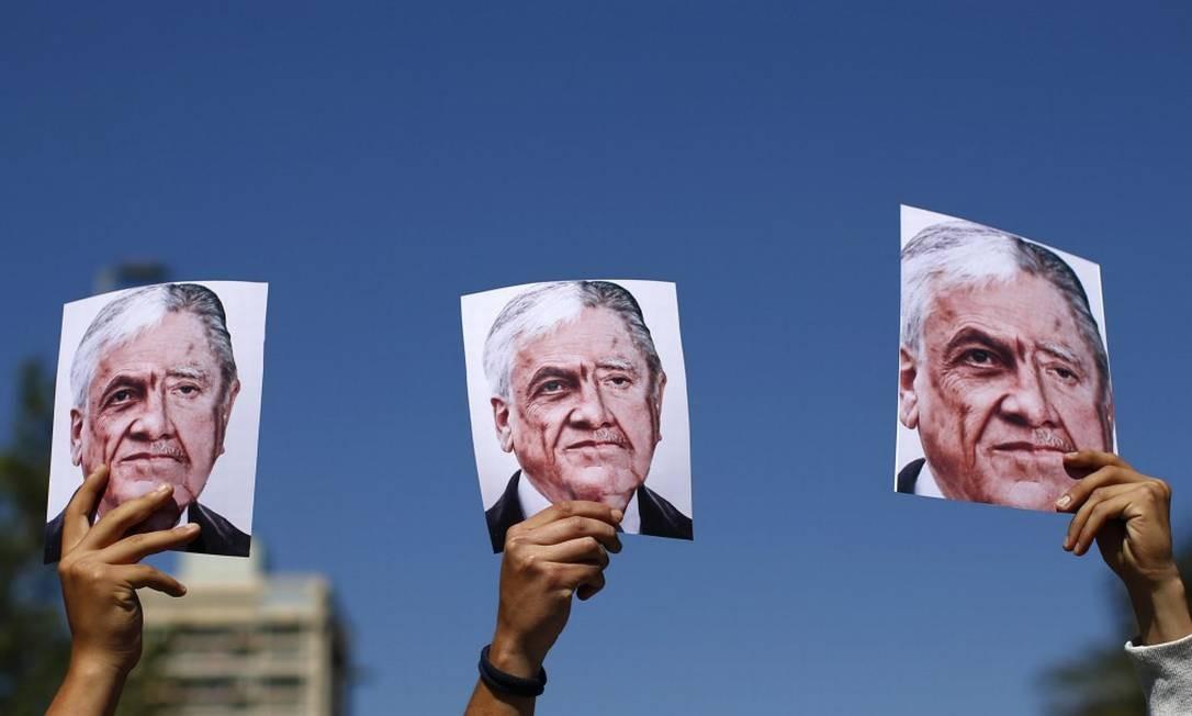 Manifestantes carregam cartazes que mostram, lado a lado, os rostos de Sebastián Piñera e Augusto Pinochet Foto: PABLO VERA / AFP