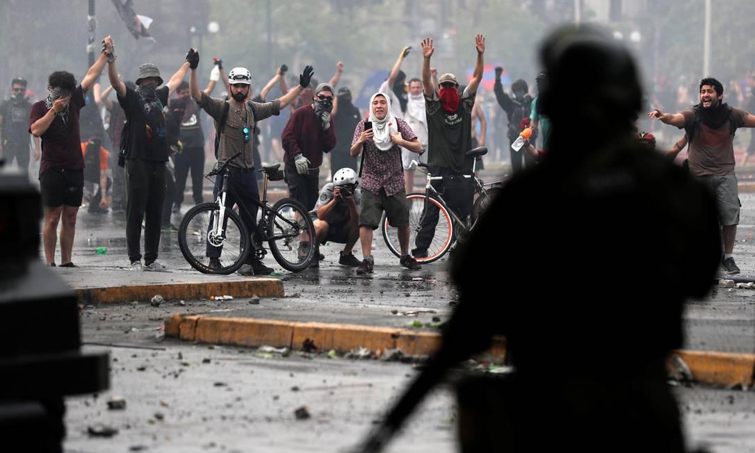 Manifestantes erguem os braços em frente às forças de segurança em protesto em Santiago: novos confrontos foram registrados nas manifestações, que continuaram nesta quarta apesar do anúncio de um pacote de medidas sociais pelo governo Foto: IVAN ALVARADO/REUTERS