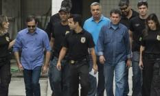 Edson Albertassi (à esquerda, de óculos escuros) e Paulo Melo (à direita, de camisa azul e bigode) deixam o IML após prisão na Cadeia Velha Foto: Guito Moreto / Agência O Globo